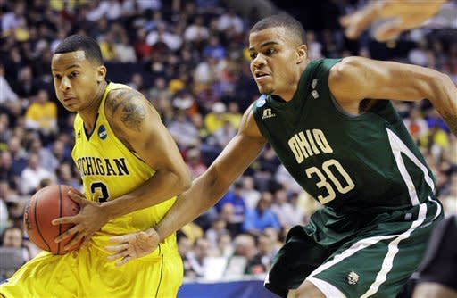 Michigan guard Trey Burke, left, drives against Ohio forward Reggie Keely (30) in the first half of a second-round NCAA college basketball tournament game on Friday, March 16, 2012, in Nashville, Tenn. (AP Photo/Mark Humphrey)