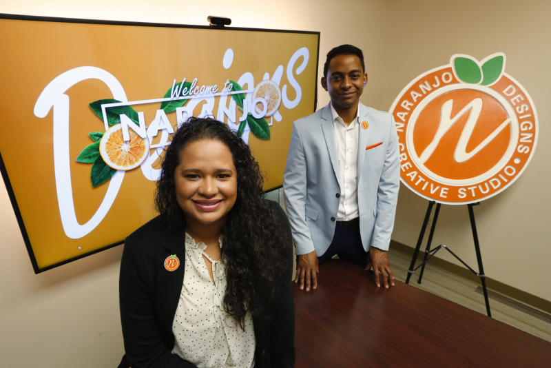In this Thursday, May 21, 2020, photo, Jessika-Katherine Naranjo Colina, left, and Bernard Kanjoma, who co-own the graphic design and marketing firm Naranjo Designs, pose for a photo in Detroit. Kanjoma, who emigrated to the United States from Malawi, said their 12-person team has seen an 80% drop in business but they're identifying creative ways to weather the crisis. (AP Photo/Paul Sancya)