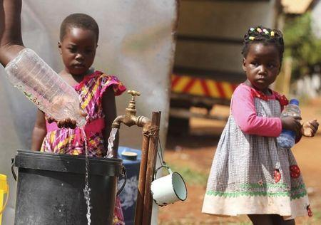 Zimbabwean children watch as their mother collects water from a communal tap in Harare