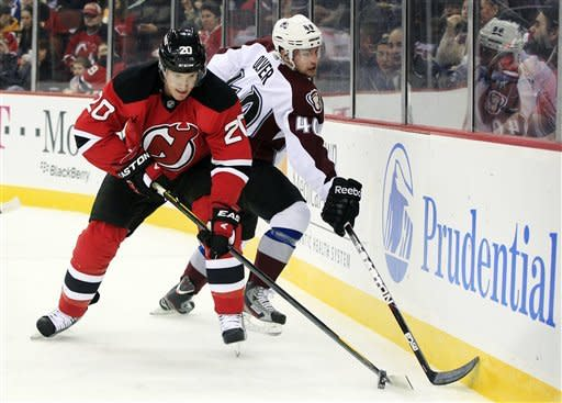 Colorado Avalanche's Mark Olver (40) can't reach the puck against New Jersey Devils' Ryan Carter (20) during the first period of an NHL hockey game in Newark, N.J., Thursday, March 15, 2012. (AP Photo/Mel Evans)