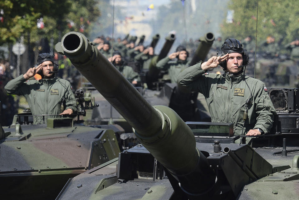 FILE - In this file photo taken Aug.15, 2017 in Warsaw, Poland, Polish Army tank troops salute as their tanks roll on one of the city's main streets during a yearly military parade celebrating the Polish Army Day. Defense Minister Mariusz Blaszczak says Poland will boost its military presence in the east with the formation of a new division of the armed forces. (AP Photo/Alik Keplicz, file)