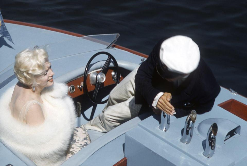 <p>Marilyn Monroe looks red carpet ready as she boards a speed boat on the set of <em>Some Like It Hot</em> in 1958. The actress dons a sequin gown, white fur stole, and diamond statement earrings for the film.</p>