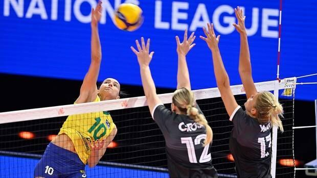 An inexperienced Canadian women's team, right, surprised Brazil by winning the first set in its Volleyball Nations League debut on Tuesday before the world No. 3 Brazilians reeled off three consecutive wins in the preliminary round matchup in Rimini, Italy. (Submitted by volleyballworld.com - image credit)