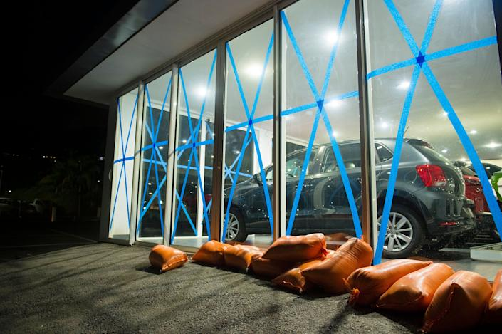 Windows of a car dealer are protected by tape and sandbags, on September 4, 2017 in Marigot.