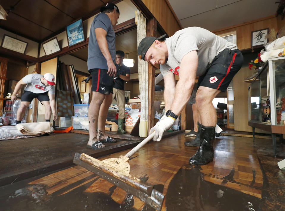 In this Oct. 13, 2019, photo, Canadian player Peter Nelson, right, volunteers to clean up mud in a house in Kamaishi, Iwate prefecture, Japan, following the cancellation of their Rugby World Cup Pool B match against Namibia due to Typhoon Hagibis. (Kyodo News via AP)