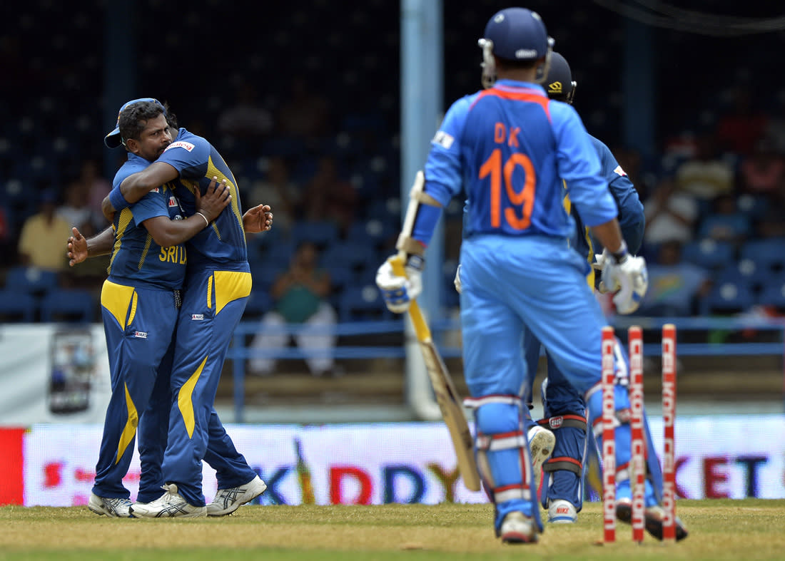 Sri Lankan cricketer Rangana Herath (L) celebrates after bowling out Indian batsman Dinesh Karthik (R) during the sixth match of the Tri-Nation series between India and Sri Lanka at the Queen's Park Oval stadium in Port of Spain on July 9, 2013. Sri Lanka won the toss and elected to field first. AFP PHOTO/Jewel Samad