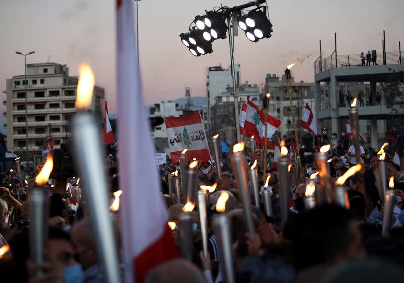 People carry torches during a demonstration marking one year since the start of nation-wide protests near Beirut's port