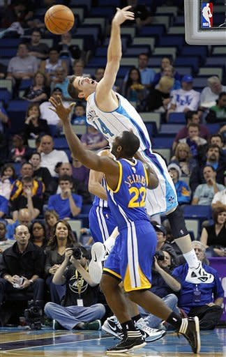 New Orleans Hornets forward Jason Smith (14) leaps for a loose ball over Golden State Warriors guard Charles Jenkins (22) in the first half of an NBA basketball game in New Orleans, Wednesday, March 21, 2012. (AP Photo/Gerald Herbert)