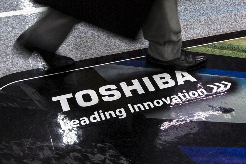 Man walks past logo of Toshiba Corp at electronics store in Tokyo