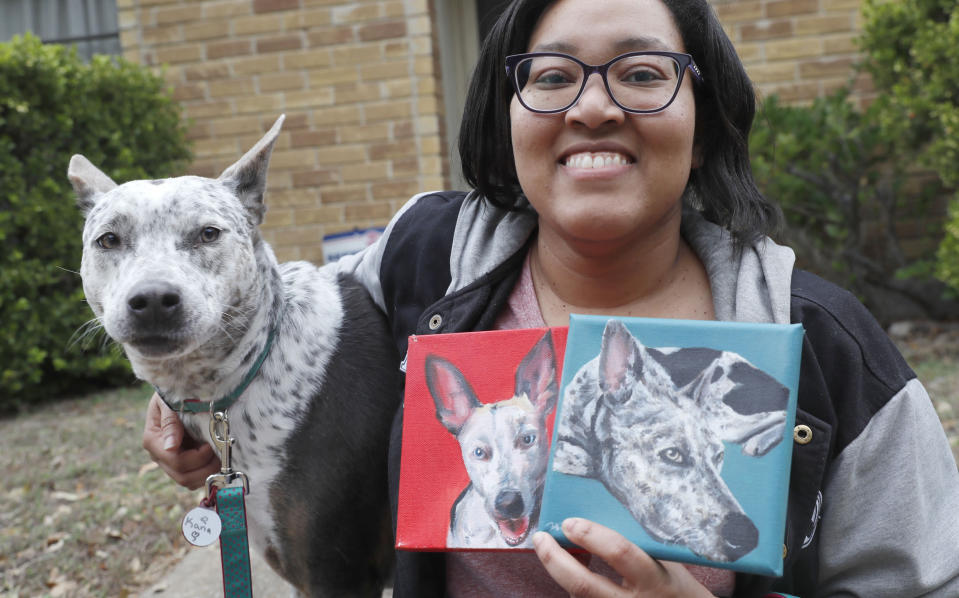 In this photo made Monday, March 2, 2020, Danielle Moore poses for photos with Kana and also paintings of the pet Australian cattle dog in Dallas. In the dog-eat-dog world of online shopping, Chewy has an unusual plan to fend off Amazon: turning pets into works of art. The online pet shop surprises customers with oil paintings of their furry friends, a move the company says wins them customers for life. (AP Photo/LM Otero)
