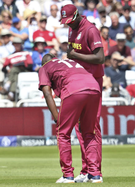 West Indies' captain Jason Holder, right, attend to teammate Andre Russell before he walked off the filed during the Cricket World Cup match between Australia and West Indies at Trent Bridge in Nottingham, Thursday, June 6, 2019. (AP Photo/Rui Vieira)