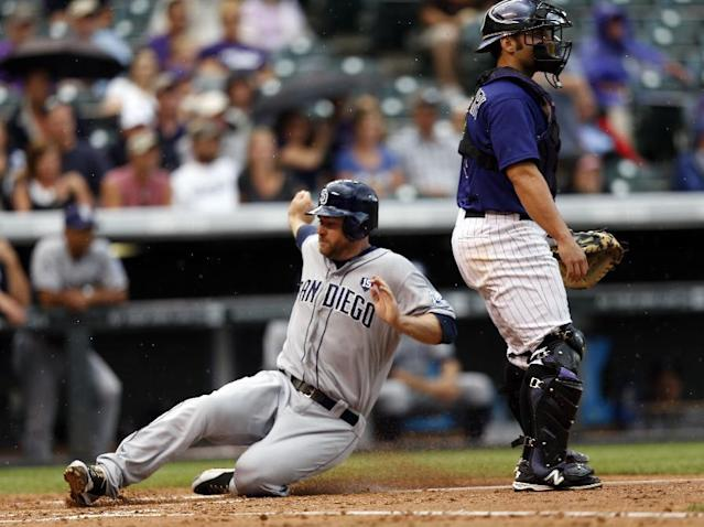 San Diego Padres' Chase Headley scores on a Brooks Conrad sacrifice fly as Colorado Rockies catcher Michael McKenry wartches the field during the fourth inning of an MLB baseball game on Monday, July 7, 2014, in Denver (AP Photo/Jack Dempsey)