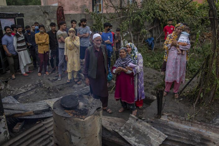 Kashmiri villagers cry near a damaged residential house where suspected rebels had taken refuge, after a gunfight in Pulwama, south of Srinagar, Indian controlled Kashmir, Wednesday, July 14, 2021. Three suspected rebels were killed in a gunfight in Indian-controlled Kashmir on Wednesday, officials said, as violence in the disputed region increased in recent weeks. Two residential houses were also destroyed. (AP Photo/ Dar Yasin)