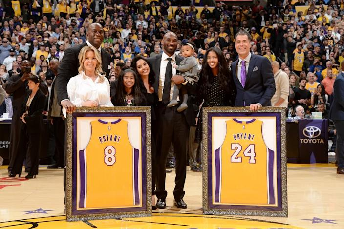 Kobe Bryant and his family pose with Magic Johnson, Jeanie Buss and Rob Pelinka during the ceremony to retire his jerseys.