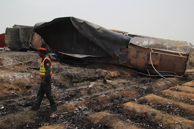 <p>Pakistani rescue workers gather beside an oil tanker which caught fire following an accident on a highway near the town of Ahmedpur East, some 670 kilometres (416 miles) from Islamabad on June 25, 2017. (Ss Mirza/AFP/Getty Images) </p>
