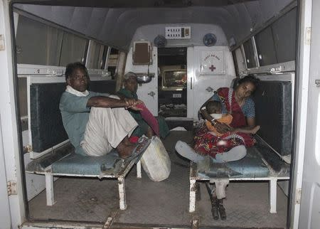 "A woman (R), who underwent a botched sterilization surgery at a government mass sterilization ""camp"", feeds her baby as she sits inside an ambulance while being moved to Chhattisgarh Institute of Medical Sciences (CIMS) hospital from a district hospital in Bilaspur, in Chhattisgarh, November 10, 2014. REUTERS/Stringer"