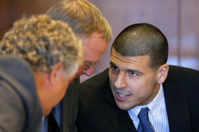Aaron Hernandez (R), former player for the NFL's New England Patriots football team, talks to defense attorneys Michael Fee (L) and Charles Rankin during a court appearance at the Bristol County Superior Court in Fall River, Massachusetts October 9, 2013, in connection with the death of semi-pro football player Odin Lloyd in June. Hernandez, who was a rising star in the NFL before his arrest and release by the Patriots, has pleaded not guilty. REUTERS/Brian Snyder (UNITED STATES - Tags: CRIME LAW SPORT FOOTBALL)
