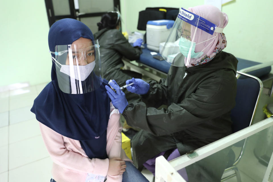 An elementary school student, wearing a face mask as a precaution against the coronavirus outbreak, receives a Td vaccine shot from a health worker during a free vaccination service for schoolchildren in Jakarta, Indonesia, Tuesday, Oct. 27, 2020. (AP Photo/Achmad Ibrahim)