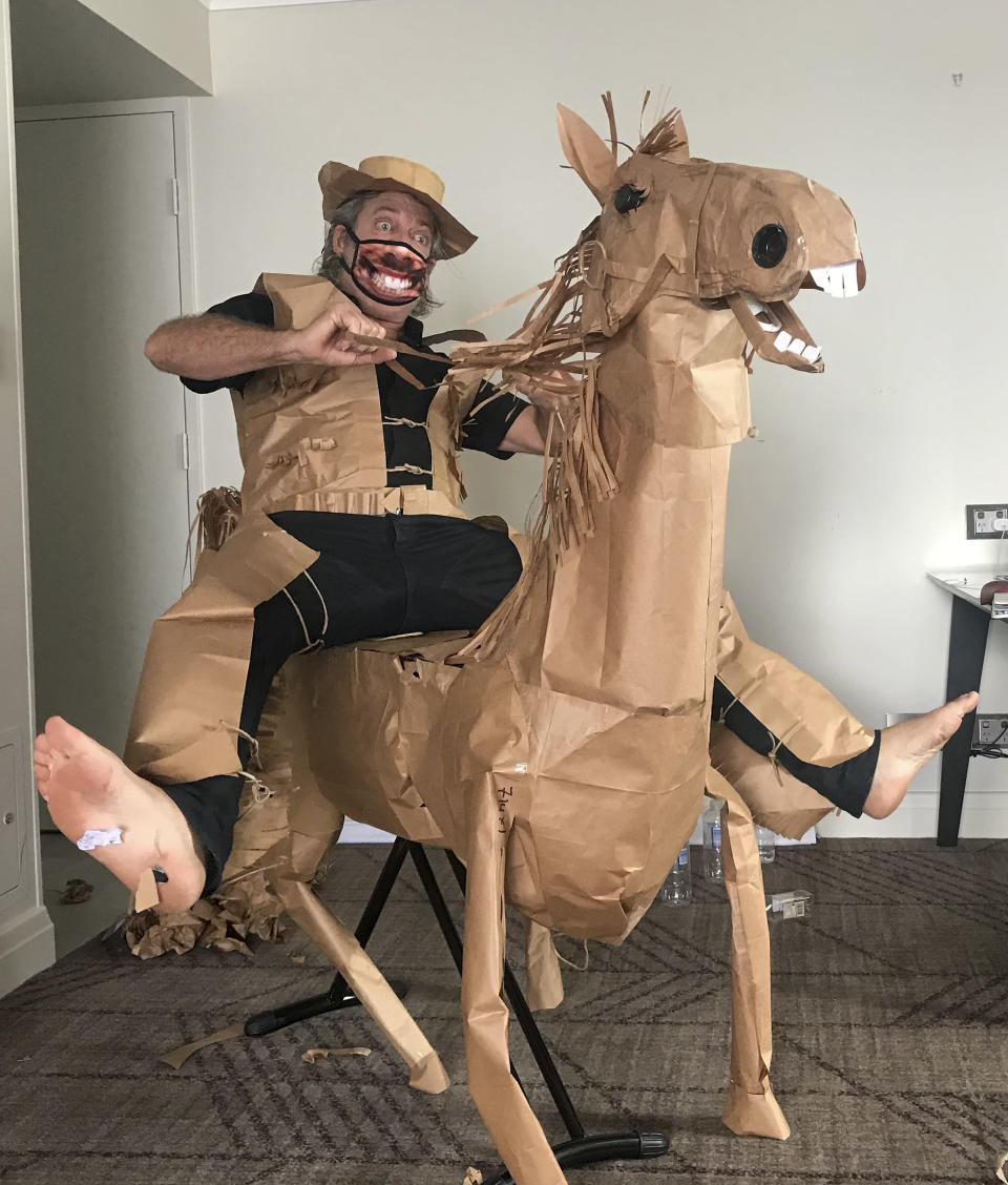 "CORRECTS NAME - David Marriott poses with his paper horse ""Russel"" in his hotel room in Brisbane, Australia, April 1, 2021. While in quarantine inside his Brisbane hotel room, the art director was bored and started making a cowboy outfit from the paper bags his meals were being delivered in. His project expanded to include a horse and a clingfilm villain that he has daily adventures with, in images that have gained a huge online following. (David Marriott via AP)"