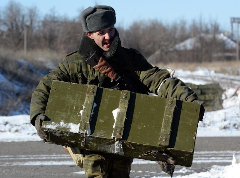 A pro-Russian rebel carries ammunition to be loaded onto a truck near the eastern Ukrainian city of Debaltseve on February 17, 2015