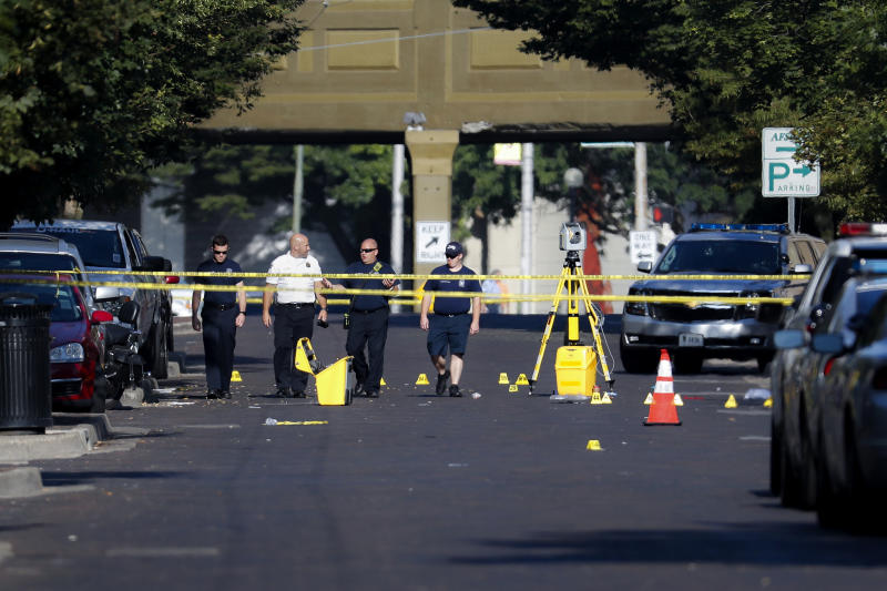 FILE - In this Aug. 4, 2019 file photo, authorities walk among evidence markers at the scene of a mass shooting  in Dayton, Ohio.  As soon as six Ohio police officers hailed as heroes killed the gunman to end an attack that claimed nine lives in Dayton, police began work to save the wounded. Their at-the-scene aid was the latest example of how police have taken on an increased medical role in mass shootings, among any adjustments in tactics, weapons, equipment and training U.S. law enforcement agencies have made as shootings have mounted. (AP Photo/John Minchillo, File)