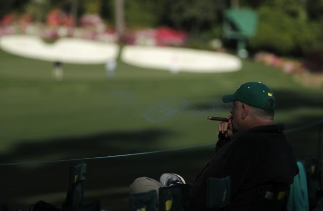"A patron gets his chair down early and enjoys a cigar while having a view of ""Amen Corner"" during second round play of the 2018 Masters golf tournament at the Augusta National Golf Club in Augusta, Georgia, U.S., April 6, 2018. REUTERS/Jonathan Ernst"