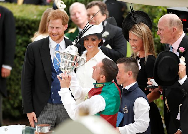 Horse Racing - Royal Ascot - Ascot Racecourse, Ascot, Britain - June 19, 2018 Frankie Dettori celebrates with a trophy after winning the 4.20 St James's Palace Stakes as Britain's Prince Harry and Meghan, the Duchess of Sussex look on Action Images via Reuters/Andrew Boyers