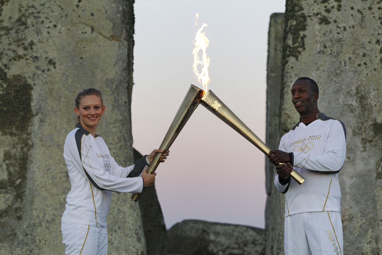 U.S. Olympian sprinter Michael Johnson, right, passes the Olympic Flame to torchbearer Emilia Clifford, 19, at Stonehenge, England, Thursday, July 12, 2012. Johnson, who He won four Olympic gold medals and eight world championship gold medals, currently holds the world and Olympic records in the 400 meters and 4 x 400 meters relay. The Olympic Torch is being carried around England in a relay of torchbearers to make its way to the London 2012 Olympic Games opening ceremony. (AP Photo/Lefteris Pitarakis)