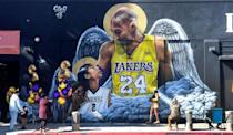 People gather in front of a mural of former Los Angeles Laker Kobe Bryant and his daughter Gianna by artist sloe_motions downtown Los Angeles