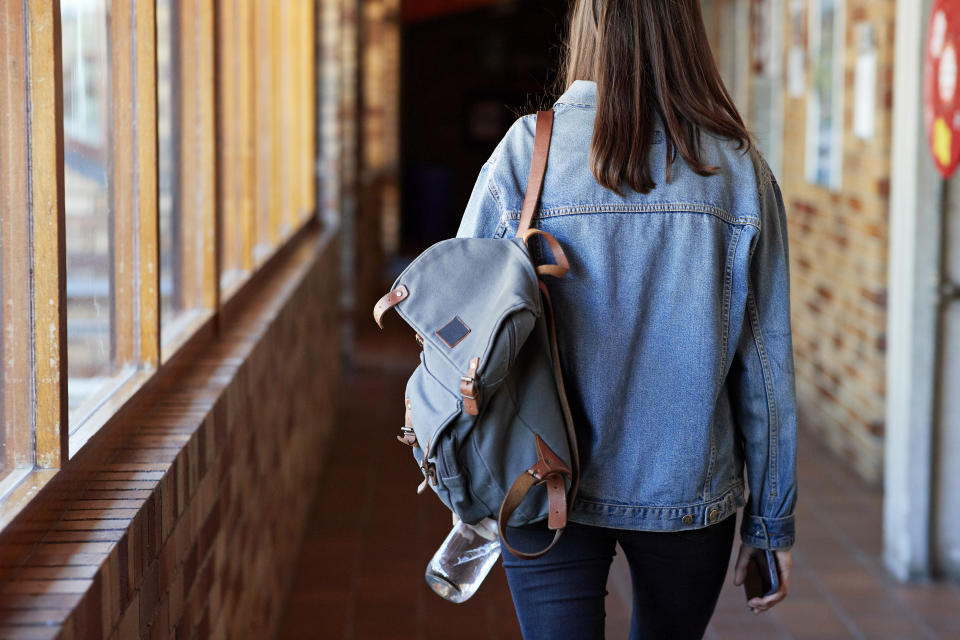 Rear view of young woman with backpack walking in corridor at university
