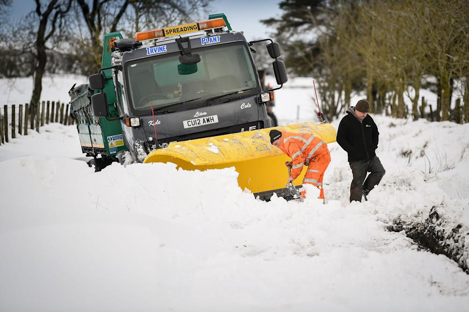 Men clear snow around a plough which had become stuck in a snow drift in Lamancha, Scotland.  (Photo: Jeff J Mitchell via Getty Images)