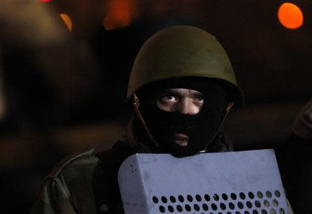 An anti-government protester watches riot police from the barricade in Kiev February 7, 2014. REUTERS/David Mdzinarishvili