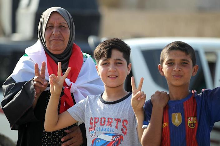 """Iraqi civilians flash the sign for victory as they celebrate in the Old City of Mosul on July 9, 2017 after the government's announcement of the """"liberation"""" of the embattled city (AFP Photo/AHMAD AL-RUBAYE)"""