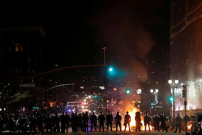 <p>Police officers form a line after demonstrators set a street on fire on Telegraph Avenue in Oakland, Calif., on Nov. 9, 2016. (Photo: Stephen Lam/Reuters) </p>