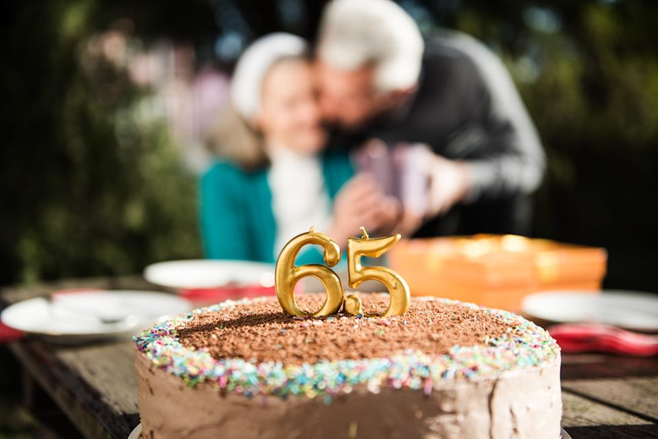 Happy senior woman receiving present from her husband on a birthday party at home backyard. Husband kissing his wife