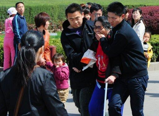 Chinese security officers arrest an elderly woman outside the Great Hall of the People which serves as the parliament building for the Communist Party of China, a day after the sacking of politician Bo Xilai from the countries powerful Politburo, in Beijing on April 11, 2012