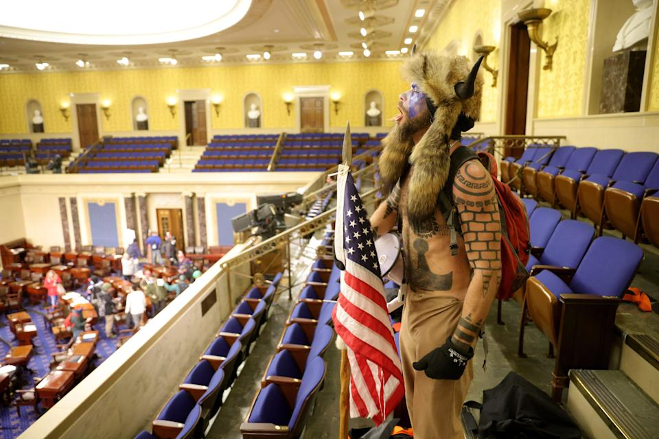 Jacob Anthony Chansley, aka Jake Angeli of Phoenix, occupies the Senate chamber on Jan. 6 after rioters broke into the U.S. Capitol.