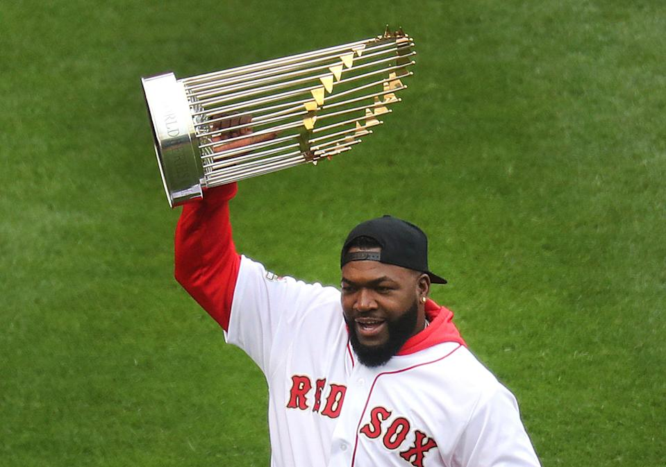 Former Boston Red Sox player David Ortiz holds up the World Series trophy during pre-game ceremonies. The Boston Red Sox host the Toronto Blue Jays in their home opener for the 2019 MLB season at Fenway Park in Boston on April 9, 2019.