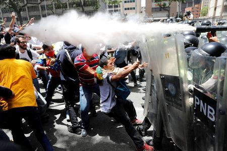 Demonstrators clash with security forces during an opposition rally in Caracas