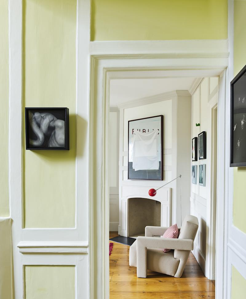 Looking through the hallway to the study, an Utrecht chair from Aram is glimpsed in front of one of the house's corner fireplaces. Over the fireplace is a painting by Rubén Guerrero. The Ballfinger wall-mounted light came from Howe, Pimlico Road; the pillow on the chair is from a favorite shop of the couple's, Chiarastella Cattana in Venice; and the oil painting to the left of the doorway is by Basque artist Alain Urrutia.