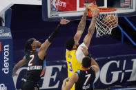 Los Angeles Lakers forward Anthony Davis (3) dunks in front of Oklahoma City Thunder guard Shai Gilgeous-Alexander (2) and forward Darius Bazley (7) during the first half of an NBA basketball game Wednesday, Jan. 13, 2021, in Oklahoma City. (AP Photo/Sue Ogrocki)