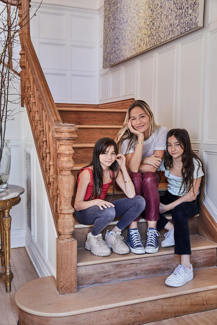 "<div class=""caption""> Dahan and her daughters hang out on the staircase she sanded by hand. A Lucien Smith piece hangs above. </div>"