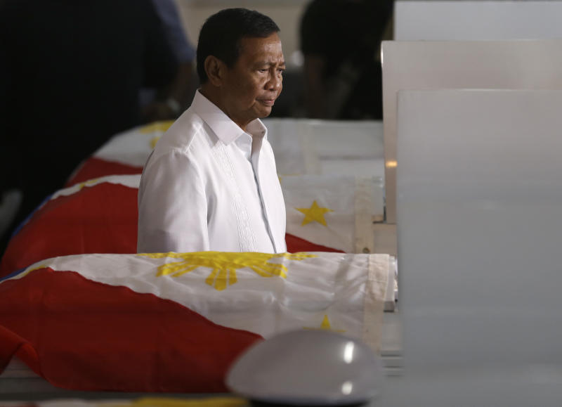 Philippine Vice-President Jejomar Binay payS tribute to seven marines killed Saturday in a clash with Abu Sayyaf militants in Jolo, southern Philippines, during the wake at the Philippine Marines headquarters at Fort Bonifacio in Taguig city, east of Manila, Philippines Monday May 27, 2013. At least seven Filipino marines and an equal number of Abu Sayyaf militants were killed in a clash in a new U.S.-backed offensive aimed at rescuing six foreign and Filipino hostages and stopping the al-Qaida-linked gunmen from staging more kidnappings in the country's south, a military commander said Sunday. (AP Photo/Bullit Marquez)