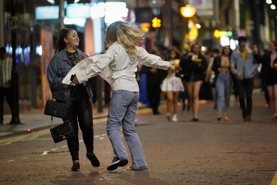 """LIVERPOOL, ENGLAND - OCTOBER 13: Revelers enjoy their last night out in the city centre as tomorrow the """"very high"""" risk lockdown regulations come into effect on October 13, 2020 in Liverpool, England. As the British government announced a new three-tier system for ranking the severity of local COVID-19 spread, the Liverpool City Region was immediately ranked """"very high"""" risk, forcing its pubs, bars, gyms and leisure centres to close from Wednesday. (Photo by Christopher Furlong/Getty Images)"""