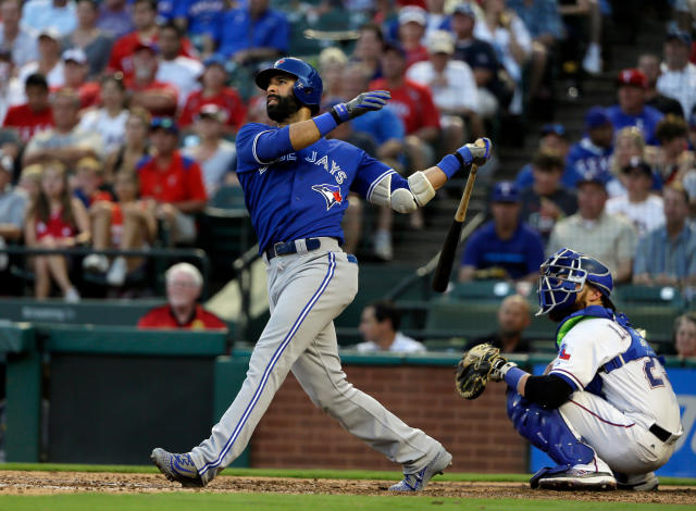 FILE - In this June 20, 2017, file photo, Toronto Blue Jays' Jose Bautista follows through on a fly out to center in the fourth inning of a baseball game as Texas Rangers catcher Jonathan Lucroy, right, watches, in Arlington, Texas. Six-time All-Star Jose Bautista and the Atlanta Braves have agreed to a minor league contract Under the deal announced Wednesday, April 18, 2018. Bautista would receive a $1 million, one-year deal if added to the 40-man major league roster. (AP Photo/Tony Gutierrez, File)
