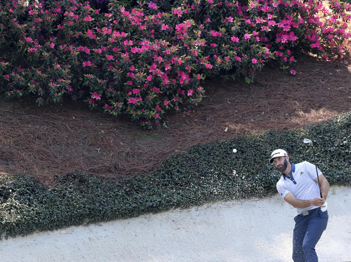 The azaleas are beginning to pop as Dustin Johnson hits his bunker shot to the 12th green during his practice round for the Masters at Augusta National Golf Club on Tuesday, April 6, 2021, in Augusta, Ga. (Curtis Compton/Atlanta Journal-Constitution via AP)