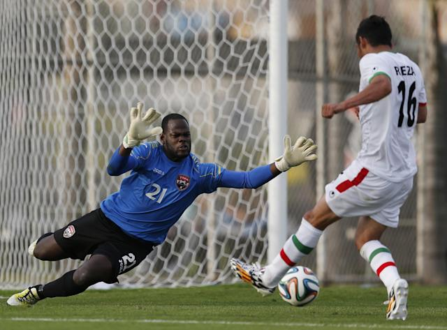 Trinidad and Tobago's national soccer team goalkeeper Jan Michael Williams, left, defends against Iran's Reza Ghouchannejad during the second half of an international soccer friendly at the Corinthians soccer team training center Sao Paulo, Brazil, on Sunday, June 8, 2014. Iran will play in group F of the 2014 soccer World Cup. (AP Photo/Julio Cortez)