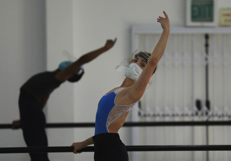 Cape Town City Ballet company dancer Olivia Parfitt, wearing a face mask and shield as she does exercises when the company returned for their first day back at work after more than two months in lockdown in Cape Town, South Africa, Friday, June 5, 2020. The dancers have been training at home due to strict lockdown regulations that have been implemented in a bid to prevent the spread of coronavirus. (AP Photo/Nardus Engelbrecht)