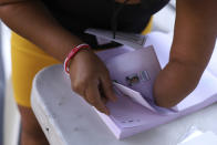 A poll worker with a missing hand, grabs ballots during local and legislative elections, at a polling place in the Zona Rosa district of San Salvador, El Salvador, Sunday, Feb. 28, 2021. Sunday's elections in El Salvador are seen as a referendum on whether to break the congressional deadlock that has tied the hands of upstart populist President Nayib Bukele. (AP Photo/Salvador Melendez)