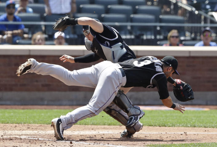 <p>Colorado Rockies catcher Tony Wolters, left, and Daniel Descalso collide as Wolters catches a foul ball by New York Mets' Wilmer Flores during the fourth inning of a baseball game, July 28, 2016, in New York. (Photo: Frank Franklin II/AP)</p>